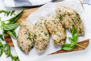 raw chicken pulled out of a marinade sitting on paper towels