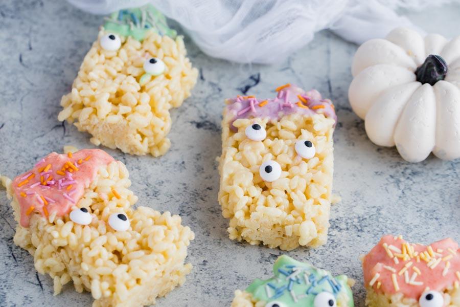 a white pumpkin next to a couple of monster rice crispy treats