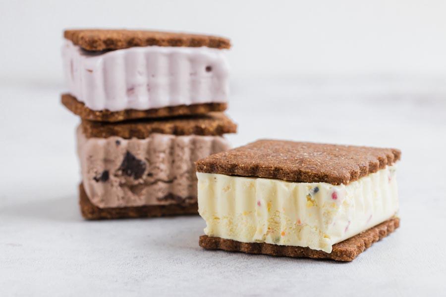 three ice cream sandwiches a vanilla, chocolate and raspberry