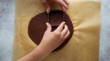 punching cookies out with a scalloped cookie cutter