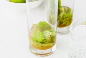 mint leaves at the bottom of a high ball glass