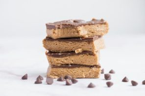 a stack of peanut butter bars with a bite out of the top one