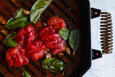 simmering tomatoes with broth and basil