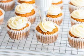 piping cream cheese frosting on a pumpkin muffin