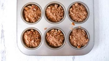 pecan streusel topping next to muffin pan with pumpkin batter inside