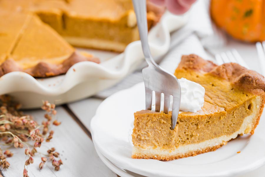 cutting a fork into a slice of pumpkin pie