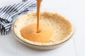 pouring pumpkin pie filling to a pie crust