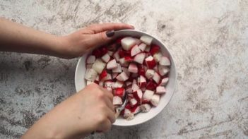 stirring a bowl of diced radishes with a spoon