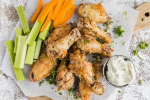 crispy wings on parchment paper served with celery sticks and julienned bell pepper