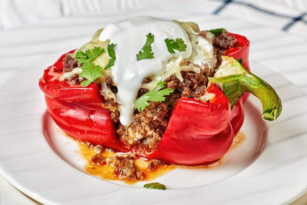 creamy sour cream dripping the top of a stuffed keto pepper