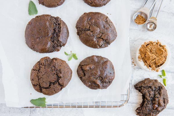cookies on a wire tray with measuring spoons, cocoa powder and mint sprigs near
