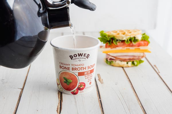 pouring hot water from a kettle into a portable keto tomato soup cup