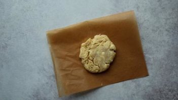 a baked cookie with white chips on parchment paper