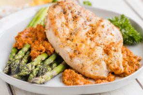 juicy romesco chicken and baked asparagus on a dinner plate