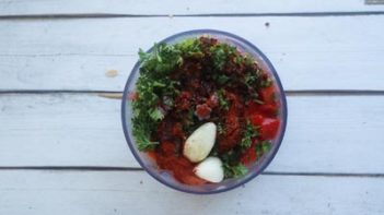 parsley, garlic and red peppers in a mini food chopper