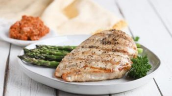 a grilled chicken breast on a plate with asparagus