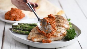 pouring romesco sauce on grilled chicken