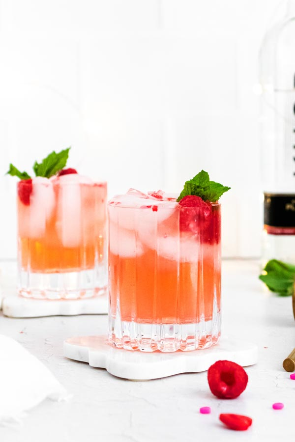 two cocktails in glasses topped with raspberries