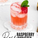 a rose spritzer pink drink with ice and raspberries