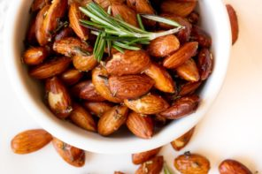 a white bowl with a bunch of seasoned almonds in it topped with rosemary