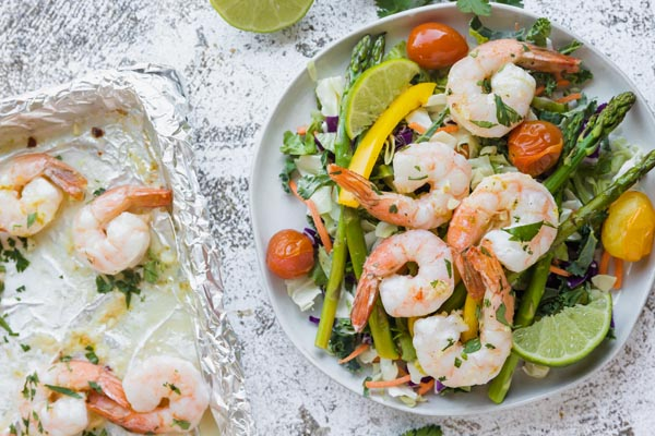 cooked shrimp topped on a salad with a tray of shrimp