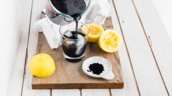pouring sugar free charcoal lemonade into a glass with ice