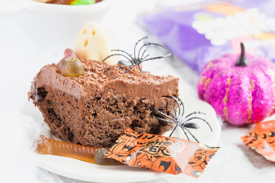 slice of keto chocoalte cake covered in spiders and gummy worms