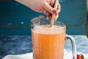 stirring a pitcher of strawberry lemonade with a wooden spoon