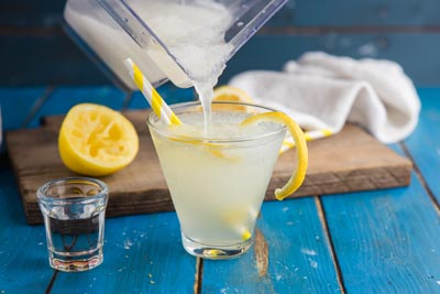 pouring a glass of vodka lemonade drink
