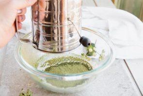 sifting green tea powder into a bowl using a sifter