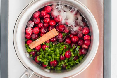 saucepan with cranberries, jalapeno and cinnamon stick