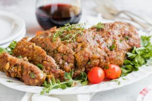 meatloaf plated with whole tomatoes next to it