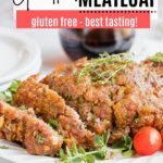 cooked meatloaf on a platter with fresh herbs